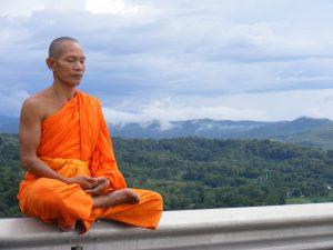 mindful leren leven: Je innerlijke wereld weerspiegelt hoe mindful jij nu bent, op de foto een boeddhistische monnik in meditatie, oranje kleding en een landschap achter zich, hij mediteert op een balustrade.