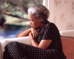 Negatieve gedachten stoppen in kleine stapjes, een oudere vrouw zit op de bank en staart naar buiten, haar gedachten lijken somber