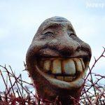 Waarom is lachen gezond voor je geest, op de foto een stenen beeld van een lachende kop met enorme tanden, een mens, maar ook weer niet