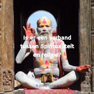 wat is spiritualiteit en hoe verhoudt dit zich tot bestaande religies? Op de foto een mediterende yogi, die is beschilderd met gele en rode kleuren en symbolen, hij zit in de lotushouding.