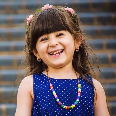 Hoe word ik weer vrolijk: gelukkig zijn mag! Op de foto een lief klein meisje met lang bruin haar, bloemetjes in haar haar, een blauwe jurk, een kralenketting en vooral: een prachtige lach op haar gezicht