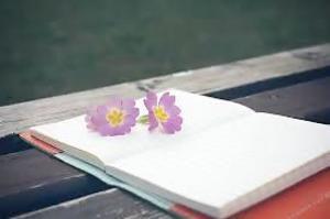 Negatieve eigenschappen positief ombuigen doe je met deze makkelijke oefening. Je hebt er een schrift of notitieblok voor nodig en een pen. Op de foto een schrift met 2 paarse bloemen erop.
