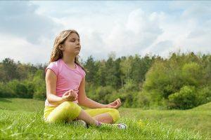 Je angst voor geesten overwinnen kan door diep te ademen zoals het meisje op de foto dat aan het mediteren is in de buitenlucht