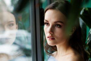 Ego loslaten of niet? Is er dualiteit of is alles een weerspiegeling? Deze vrouw ziet zichzelf in de weerspiegeling van een venster.