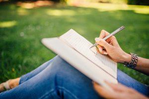 Ontdekken wie jij echt bent! Als je schrijft wie je allemaal bent ontdek je de illusies van je ego. Op de foto zie je een vrouw die aan het schrijven is in een schrift, terwijl ze in het groene gras zit.